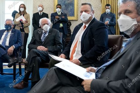 Stock Image of From left: Senator Bob Menendez (D-N.J.), Senator Bernie Sanders (I-V.T.), Senator Jon Tester (D-MT), and Senator Sherrod Brown (D-OH) wear protective masks while meeting with U.S. President Joe Biden, not pictured, to discuss the American Rescue Plan in the Oval Office of the White House