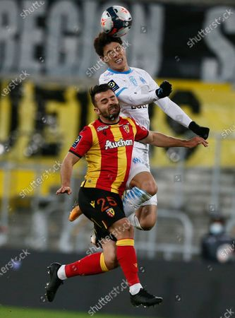 Marseille's Hiroki Sakai of Japan, top, jumps for the ball with Lens' Corentin Jean, during the French League One soccer match between Lens and Olympique Marseille at the Bollaert stadium in Lens, northern France, . The match ended 2-2 draw