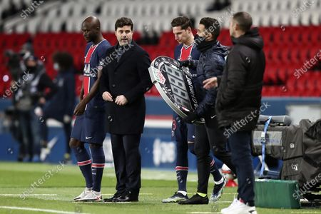 PSG's head coach Mauricio Pochettino, center, prepares his substitutions Danilo Pereira, left, and Julian Draxler during the French League One soccer match between Paris Saint-Germain and Nimes at the Parc des Princes stadium in Paris, France