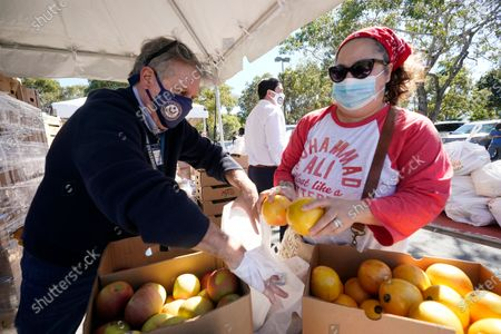 Frank Balzebre, left, director of community outreach for the office of Congressman Carlos Gimenez, and Neva McFeely, right, pack fruit into bags to be distributed, during a drive-thru food distribution event at J.D. Redd Park in Homestead, Fla