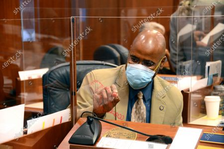 State Sen. David Wilson, R-Wasilla, draws on the plexiglass protector around the desk of Sen. Mia Costello, R-Anchorage, during an at-ease, in the Alaska State Senate at Juneau, Alaska