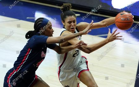 Connecticut forward Olivia Nelson-Ododa (20) drives against St. John's forward Raven Farley (4) during the first half of an NCAA college basketball game, in Storrs, Conn