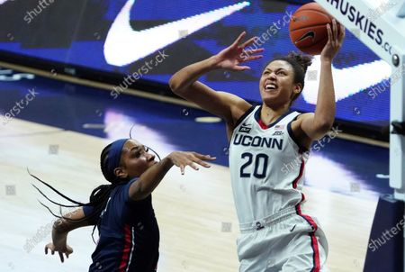 Connecticut forward Olivia Nelson-Ododa (20) shoots next to St. John's forward Raven Farley (4) during the first half of an NCAA college basketball game, in Storrs, Conn