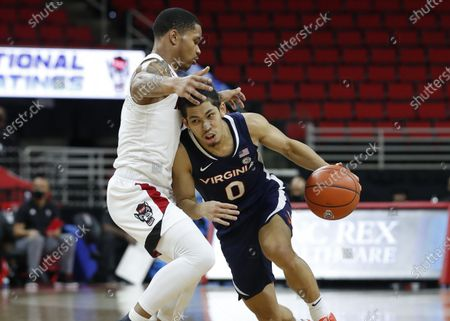 Stock Picture of Virginia's Kihei Clark (0) drives around North Carolina State's Shakeel Moore (2) during the second half of an NCAA college basketball game, in Raleigh, N.C