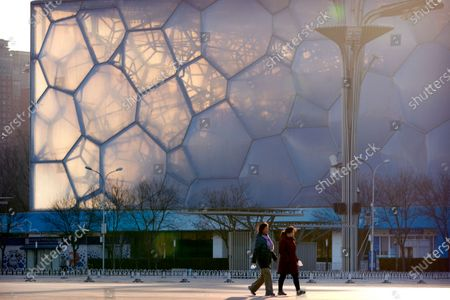 """People walk past the Water Cube, which will be known as the Ice Cube when it hosts events for the 2022 Beijing Winter Olympics, in Beijing, . The 2022 Beijing Winter Olympics will open a year from now. Most of the venues have been completed as the Chinese capital becomes the first city to hold both the Winter and Summer Olympics. Beijing held the 2008 Summer Olympics. But these Olympics are presenting some major problems. They are already scarred by accusations of rights abuses including """"genocide""""against more than 1 million Uighurs and other Muslim ethnic groups in western China"""