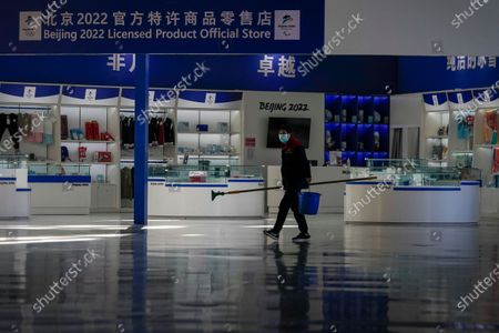 """Cleaner wearing a face mask to curb the spread of the coronavirus walks by a Beijing Winter Olympics merchandise store inside the Olympics Tower in Beijing on . The 2022 Beijing Winter Olympics will open a year from now. Most of the venues have been completed as the Chinese capital becomes the first city to hold both the Winter and Summer Olympics. Beijing held the 2008 Summer Olympics. But these Olympics are presenting some major problems. They are already scarred by accusations of rights abuses including """"genocide""""against more than 1 million Uighurs and other Muslim ethnic groups in western China"""