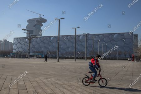 A boy rides a bicycle next to the China's National Aquatics Center, which will be known as the Ice Cube during 2022 Beijing Winter Olympics, 365 days before the 2022 Beijing Winter Olympics, in Beijing, China, 04 February 2021. The 2022 Beijing Winter Olympics are scheduled to take place from 04 to 20 February 2022. Many right groups representing Tibetans, Inner Mongolians, Hong Kong residents and Uighurs have been calling for the boycott of the 2022 Beijing Winter Olympics.