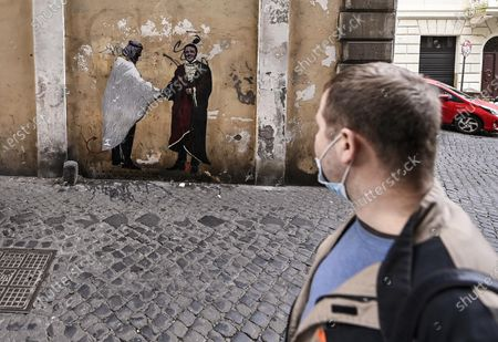A view of a large poster depicting former Italian prime minister Matteo Renzi (R) handshaking with Mohammed bin Salman, Crown Prince of Saudi Arabia (L) by an unidentified street artist aka Harry Greb in the center of Rome, Italy, 4 February 2021.