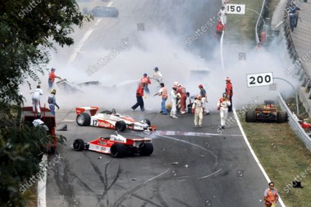Stock Picture of The immediate aftermath of the multi-car accident at the start of the race: Ronnie Peterson (SWE) Lotus (Yellow overalls) lies in the track having been pulled from his shattered, burning, Lotus 78, and is tended to by marshals, Clay Regazzoni (SUI) Shadow (Red Overalls) and Patrick Depailler (FRA) Tyrrell (Blue helmet). James Hunt (GBR) McLaren (Black helmet) walks from the scene with team mate Bruno Giacomelli (ITA) McLaren. Vittorio Brambilla (ITA) (Right) lies - head slumped -in his Surtees TS20 after suffering a serious head injury from which he fully recovered. Tragically, Peterson would die from a blood clot following an operation in hospital on his badly broken legs.