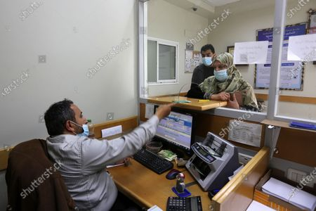 Palestinians wear protective face masks, as they wait to receive their financial aid, amid the coronavirus disease (COVID-19) outbreak, at the Post Office, in Dair Al Balah in the central of Gaza Strip, on February 4, 2021. HE Chairman of Qatar's Gaza Reconstruction Committee Ambassador Mohammed Al Emadi affirmed that since the beginning of its work in the field of Gaza reconstruction in 2012, starting with the USD 407 million grant of HH the Father Amir Sheikh Hamad Bin Khalifa Al-Thani, the Committee constituted a turning point in the field of development and reconstruction, and supervised hundreds of humanitarian projects with integrated plans to provide and meet the needs of the people of Gaza in various fields.