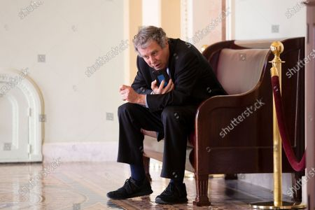 The incoming Chair of the Senate Banking, Housing and Urban Affairs Committee, Democrat of Ohio Sherrod Brown, uses a cell phone outside the Senate chamber, on Capitol Hill in Washington, DC, USA, 04 February 2021.