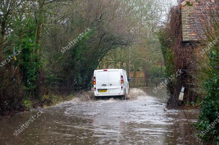 A white van drives through flood water on a closed road in Sonning. Following heavy rain over the past few days, the River Thames has burst it's banks at Sonning in Berkshire. A Flood Alert is in place and low lying roads, paths and fields have flooded. Although the B478 across Sonning Bridge is closed due to the flooding, some drivers were ignoring the road closure signs and driving through the floods