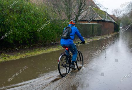 A man cycles through floodwater near Sonning Bridge. Following heavy rain over the past few days, the River Thames has burst it's banks at Sonning in Berkshire. A Flood Alert is in place and low lying roads, paths and fields have flooded. Although the B478 across Sonning Bridge is closed due to the flooding, some drivers were ignoring the road closure signs and driving through the floods