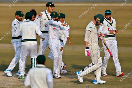 South Africa's Faf du Plessis, second right, walks back to pavilion while Pakistan's players celebrate his dismissal during the second day of the second cricket test match between Pakistan and South Africa at the Pindi Stadium in Rawalpindi, Pakistan