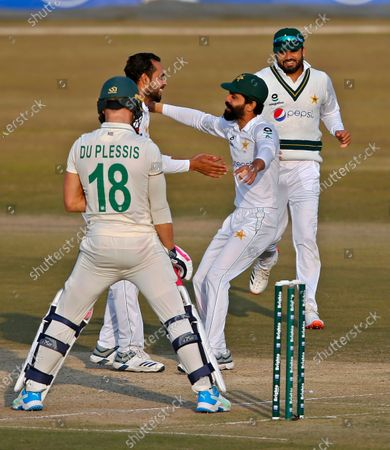 Pakistan's Faheem Ashraf, second left, celebrates with teammates after taking the wicket of South Africa's Faf du Plessis, left, during the second day of the second cricket test match between Pakistan and South Africa at the Pindi Stadium in Rawalpindi, Pakistan
