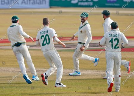 South Africa's Faf du Plessis, center, celebrates with teammates after the dismissal of Pakistan's Babar Azam during the first day of the second cricket test match between Pakistan and South Africa at the Pindi Stadium in Rawalpindi, Pakistan