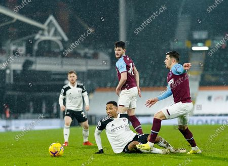 Kenny Tete of Fulham plays the ball on the floor ahead of Aaron Cresswell and Declan Rice of West Ham