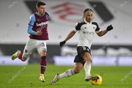Bobby De Cordova Reid of Fulham runs the ball away from Aaron Cresswell of West Ham United
