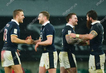 Finn Russell celebrates at full time with Chris Harris as Stuart Hogg, second right, and Gary Graham of Scotland do the same