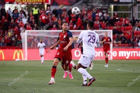 Tomi Juric of Adelaide United and Darryl Lachman of Perth Glory attack the ball during the Hyundai A-League soccer match between Adelaide United and Perth Glory FC .