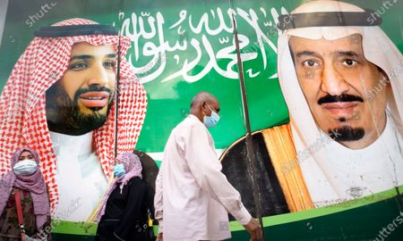 People wear face masks to protect against the spread of the coronavirus in front of a banner showing Saudi King Salman, right, and his Crown Prince Mohammed bin Salman, outside a mall in Jiddah, Saudi Arabia, . In Saudi Arabia, where authorities already have banned travel to the kingdom from 20 countries including the U.S., officials ordered all weddings and parties suspended. It closed down all shopping malls, gyms and other locations for 10 days, as well as indoor dining