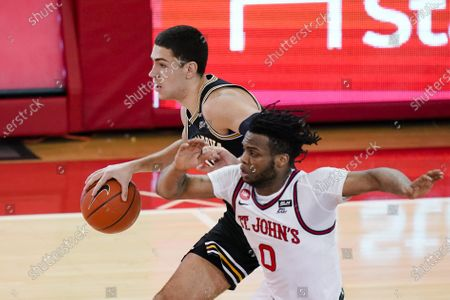 Villanova's Cole Swider, left, drives past St. John's Posh Alexander (0) during the first half of an NCAA college basketball game, in New York