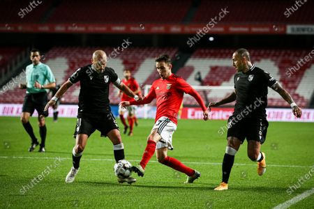 Benfica player Alejandro Grimaldo (C) vies for the ball with Vitoria Guimaraes players Andre Andre and Ricardo Quaresma (R) during the Portuguese First League soccer match Benfica vs Vitoria Guimaraes held at Luz Stadium, Lisbon, Portugal, 05 February 2021.