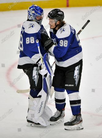 Tampa Bay Lightning goalie Andrei Vasilevskiy (88) and Mikhail Sergachev (98) celebrate a win over the Detroit Red Wings at the end of an NHL hockey game, in Tampa, Fla