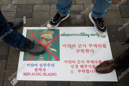 """Myanmar people living in South Korea stand over a defaced picture of Myanmar military Commander-in-Chief Senior Gen. Min Aung Hlaing during a rally against the military coup near the office of the military attache of the Myanmar embassy, in Seoul, South Korea, . The letters read """"Denouncing the military coup in Myanmar"""
