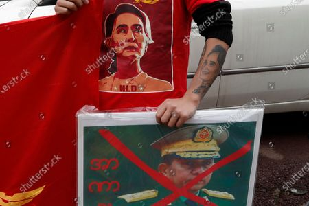 Myanmar man living in South Korea holds a banner carrying a defaced picture of Myanmar military Commander-in-Chief Senior Gen. Min Aung Hlaing during a rally against the military coup near the office of the military attache of the Myanmar embassy, in Seoul, South Korea