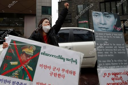 """Myanmar woman living in South Korea shouts slogans as she holds a banner with a defaced picture of Myanmar military Commander-in-Chief Senior Gen. Min Aung Hlaing during a rally against the military coup near the office of the military attache of the Myanmar embassy, in Seoul, South Korea, . The letters read """"Denouncing the military coup in Myanmar"""