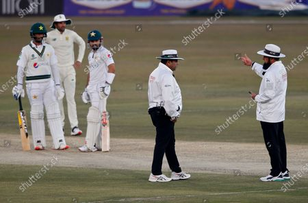 Stock Photo of Umpire Aleem Dar, right, discusses with Ahsan Raza, center, regarding light condition while Pakistan's and South Africa players watches during the third day of the second cricket test match between Pakistan and South Africa at the Pindi Stadium in Rawalpindi, Pakistan