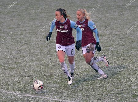 Martha Thomas (L) and Adriana Leon of West Ham United in action in the snow