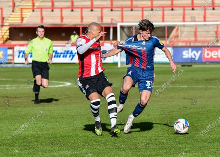 Bradford City midfielder Oliver Crankshaw (31) shields the ball from Jake Caprice (2) of Exeter City  and is pulled by his shir during the EFL Sky Bet League 2 match between Exeter City and Bradford City at St James' Park, Exeter