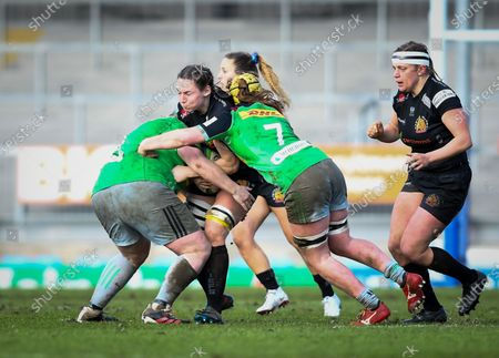 Ebony Jefferies of Exeter Chiefs is tackled by Chloe Edwards and Emily Robinson of Harlequins