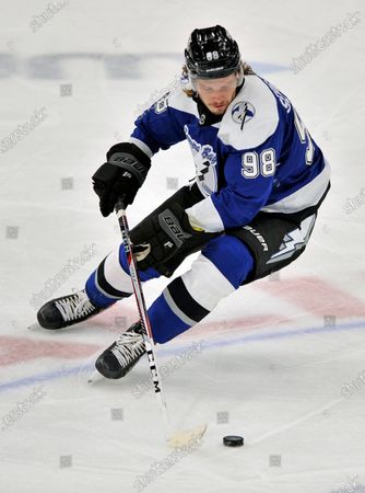 Tampa Bay Lightning's Mikhail Sergachev moves the puck during an NHL hockey game against the Detroit Red Wings, in Tampa, Fla