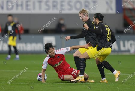 (L-R) Freiburg's Woo-yeong Jeong in action against Dortmund's Julian Brandt and Emre Can during the German Bundesliga soccer match between SC Freiburg and Borussia Dortmund in Freiburg, Germany, 06 February 2021.