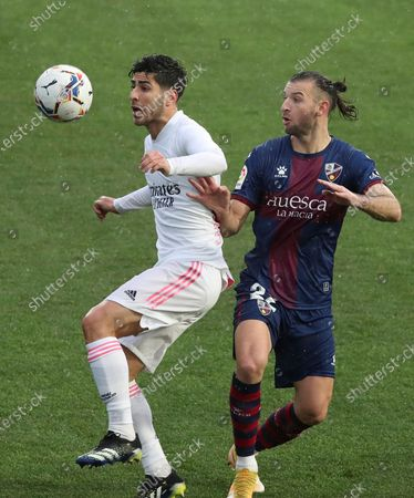 SD Huesca's Gaston Silva (R) in action against Real Madrid's Marco Asensio (L) during a Spanish LaLiga soccer match between SD Huesca and Real Madrid at El Alcoraz stadium in Huesca, Aragon, Spain, 06 February 2021.