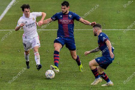 Real Madrid's Alvaro Odriozola, left, vies for the ball with Huesca's Rafa Mir, centre, during the Spanish La Liga soccer match between Huesca and Real Madrid at El Alcoraz stadium in Huesca, Spain