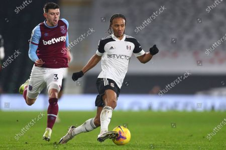 Fulham's Bobby Decordova-Reid, center, is challenged by West Ham's Aaron Cresswell during the English Premier League match between Fulham and West Ham at the Craven Cottage stadium in London