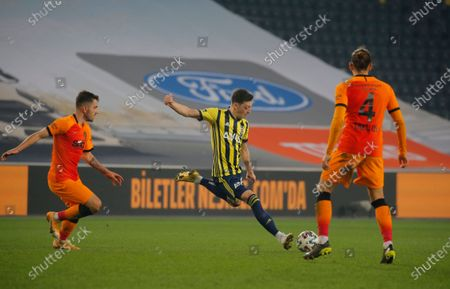 Fenerbahce's Mesut Ozil, center, of Germany, shoots the ball during a Turkish Super League soccer match between Fenerbahce and Galatasaray in Istanbul, . Ozil, who is of Turkish descent and was formerly with Arsenal came in as a substitute on his his first match with Fenerbahce. Galatasaray won the match 1-0