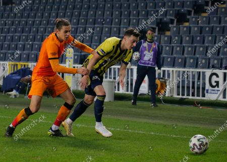 Fenerbahce's Mesut Ozil, of Germany, right, dribbles past Galatasaray's Martin Linnes, during a Turkish Super League soccer match between Fenerbahce and Galatasaray in Istanbul, . Ozil, who is of Turkish descent and was formerly with Arsenal came in as a substitute on his first match with Fenerbahce. Galatasaray won the match 1-0