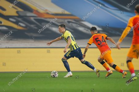 Fenerbahce's Mesut Ozil, of Germany, center dribbles past Galatasaray's Emre Kilinc, right, during a Turkish Super League soccer match between Fenerbahce and Galatasaray in Istanbul, . Ozil, who is of Turkish descent and was formerly with Arsenal came in as a substitute on his first match with Fenerbahce. Galatasaray won the match 1-0