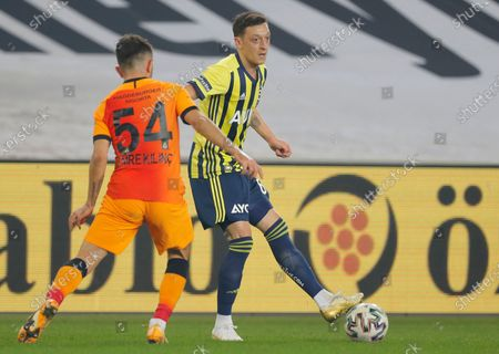 Fenerbahce's Mesut Ozil, of Germany, center shoots the ball as Galatasaray's Emre Kilinc, left, tries to stop him, during a Turkish Super League soccer match between Fenerbahce and Galatasaray in Istanbul, . Ozil, who is of Turkish descent and was formerly with Arsenal came in as a substitute on his first match with Fenerbahce. Galatasaray won the match 1-0