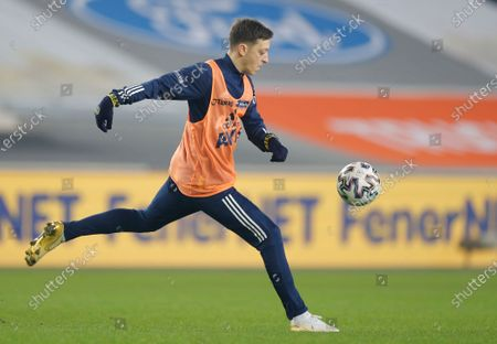 Mesut Ozil, the former Germany soccer midfielder, warms up during the half time of a Turkish Super League soccer match between Fenerbahce and Galatasaray in Istanbul, . Ozil, who is of Turkish descent and was formerly with Arsenal had signed with Fenerbahce soccer club