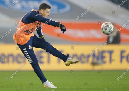 Mesut Ozil, the former Germany soccer midfielder, shoots the ball as h warms up during the half time of a Turkish Super League soccer match between Fenerbahce and Galatasaray in Istanbul, . Ozil, who is of Turkish descent and was formerly with Arsenal had signed with Fenerbahce soccer club