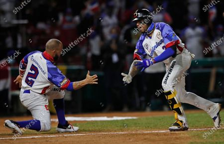 Dominican Republic's Johan Camargo, right, is congratulated by Juan Carlos Perez after hitting a solo home run against Puerto Rico during the fifth inning of the Caribbean Series baseball final at Teodoro Mariscal stadium in Mazatlan, Mexico