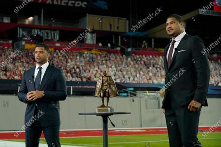 Baltimore Ravens' Calais Campbell, right, presents the Walter Payton NFL Man of the Year award to Seattle Seahawks quarterback Russell Wilson during the NFL Honors ceremony as part of Super Bowl 55, in Tampa, Fla