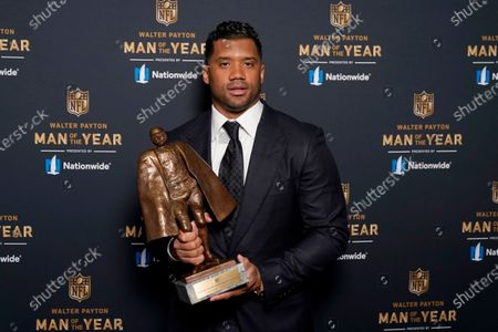 Seattle Seahawks quarterback Russell Wilson poses with his trophy after winning the Walter Payton NFL Man of the Year award during the NFL Honors ceremony as part of Super Bowl 55, in Tampa, Fla