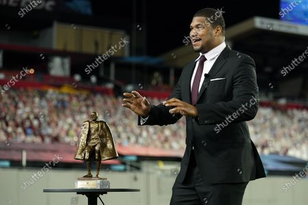 Baltimore Ravens' Calais Campbell presents the Walter Payton NFL Man of the Year award to Seattle Seahawks quarterback Russell Wilson during the NFL Honors ceremony as part of Super Bowl 55, in Tampa, Fla